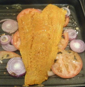 Cod fillet arranged on a bed of onion and tomatoes