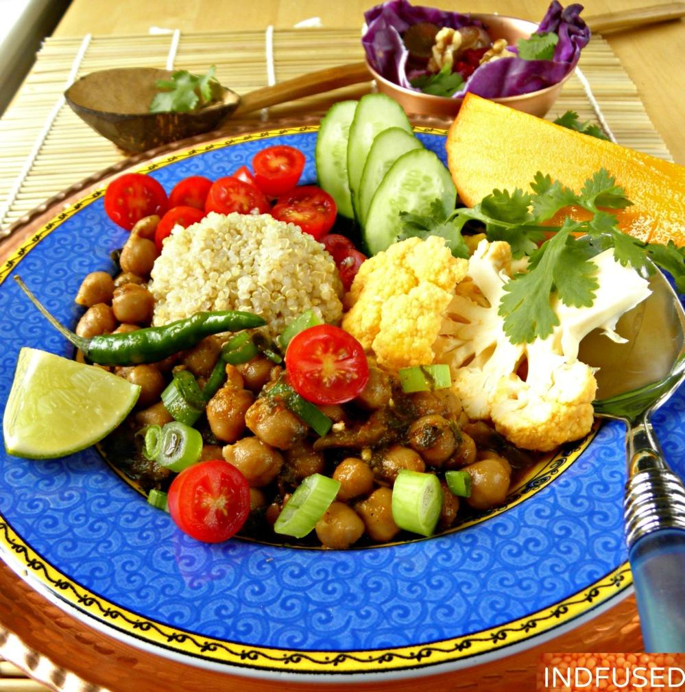 Easy recipe for Indian spiced Buddha Bowl with chana masala, quinoa, veggies, raita and mango