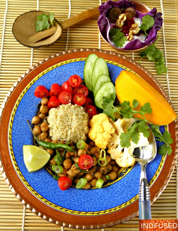 Easy recipe for Indian spiced Buddha Bowl with chana masala, quinoa, veggies, raita and mango